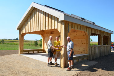 Volunteers put the 'Last Spike' or last nail into the construction of the new Woodland Reflection Shelter pavilion along the South Huron Trail.
